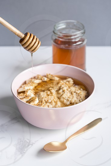 Healthy banana porridge/oatmeal with drizzle of honey. photo