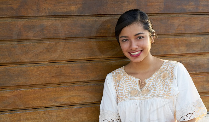 Mexican latin woman with ethnic dress smiling in wooden background photo