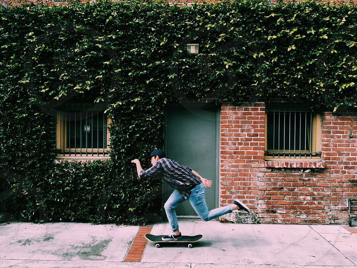 boy in black and grey checked dress shirt on skateboard in sidewalk passing ivy covered brown brick wall photo