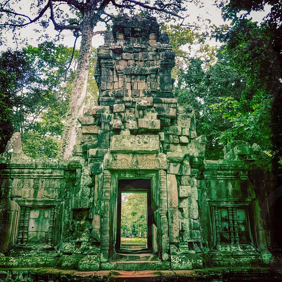 Outdoor day colour square filter Angkor Angkor National Park Siem Reap Cambodia Asia Asian east eastern ancient holy spiritual Khmer dynasty monument sky blue white clouds summer travel tourism tourist wanderlust stone carved ornate elaborate figure figures temple grounds ruin ruined trees door doorway photo