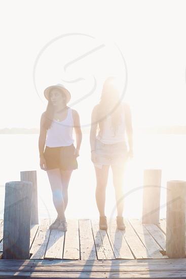 2 women standing on wooden pathway photo