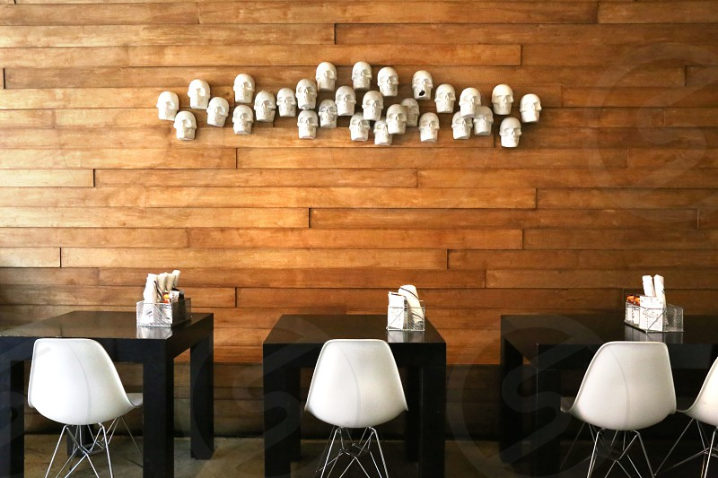 3 black square table with white chairs near brown wooden wall with white skull decor photo