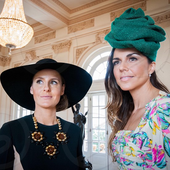 woman wearing black sun hat and black dress with gold and black floral chunky necklace beside a woman with green hairdress and floral dress inside a room with arch white glass window photo