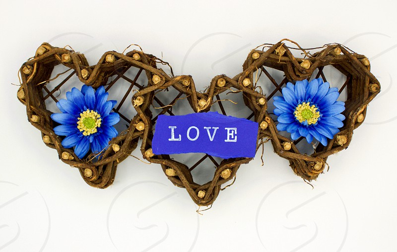 """Overhead view of three woven grapevine hearts with blue flowers on either side of the word """"LOVE"""" stamped in white ink in torn dark blue paper on a white background photo"""