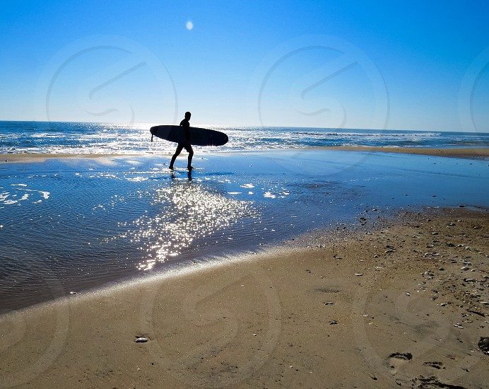 Ocean surfer sunset reflections water photo