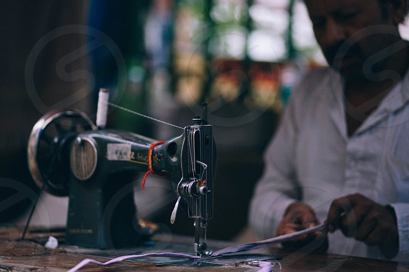Man working with a sewing machine in New Delhi India photo