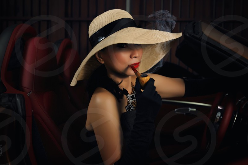 woman seated on car wearing white and black floppy hat smoking wooden pipe posing for photo photo