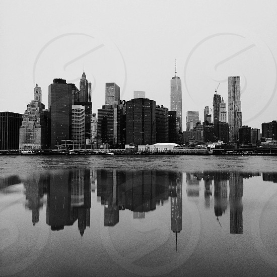 city buildings by water in grayscale photography photo