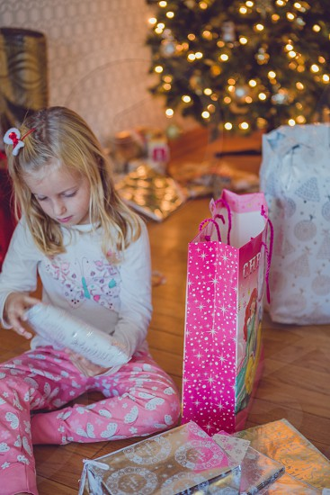 Young girl at Christmas unwrapping presents.  photo