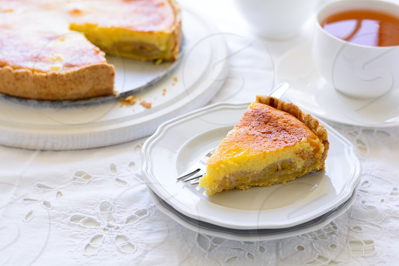 Delicious banana cake (cheesecake) with tea cup on white table. Teatime concept. Copy space photo