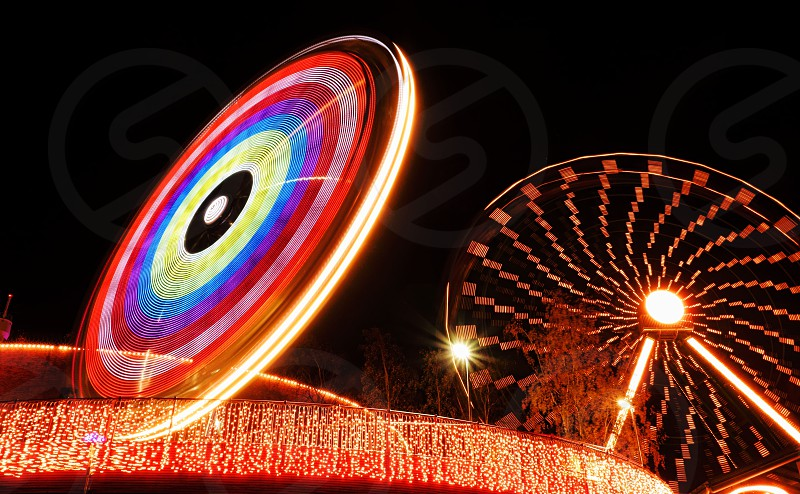 Ferris wheel and another ride at Linnanmäki amusement park during light during the Carnival of Lights festival on 21 October 2013 in Helsinki Finland.  photo