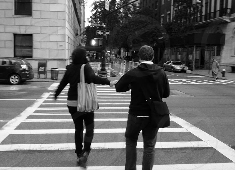 man in black hoodie walking on pedestrian lane photo
