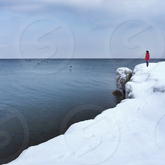 figure in red coat standing on icy shore near body of water photo