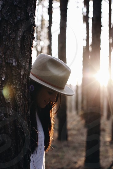 woman on beige fedora  and white knit shirt behind gray tree trunk during daytime photo