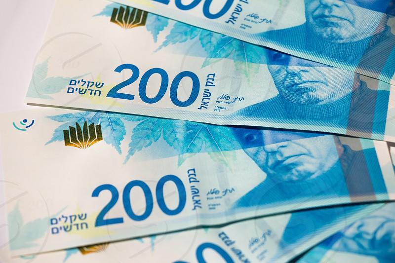 Stack of Israeli money bills of 200 shekel - top view. photo