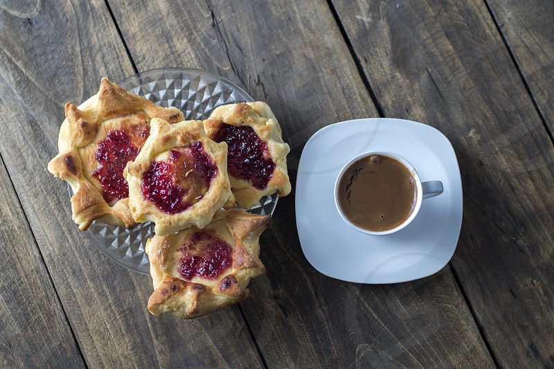 homemade puff pastry filled with strawberry jam and coffee photo