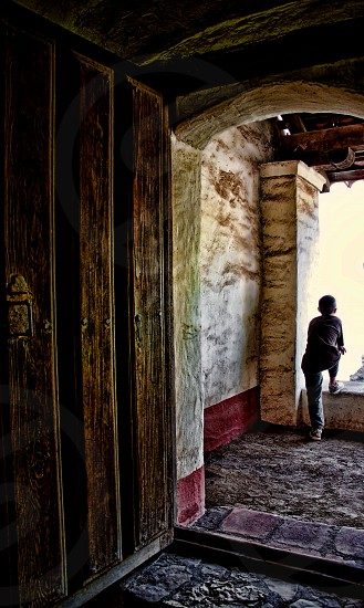 Seen from behind a boy is framed by the open door of an old wood and stone building photo