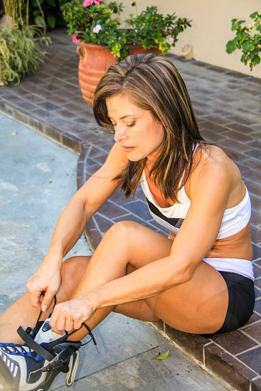 Athletic woman lacing up rollerblades photo