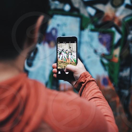person taking photo of graffiti wall photo