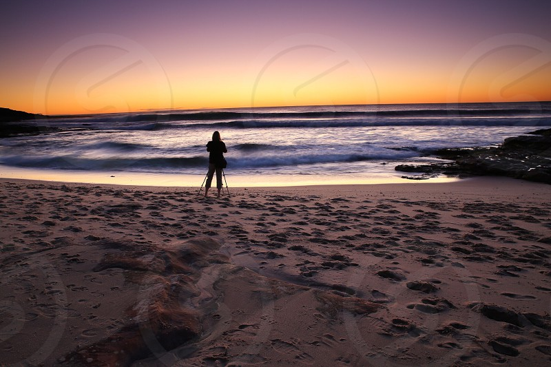 woman standing on the beach with a tripod photo
