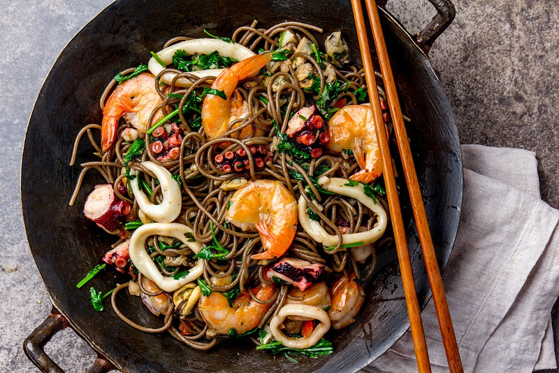 Buckwheat stir-fry noodles with seafood - shrimps octopus squid in cast iron asian wok with cooking chopstick. Top view stone background. photo