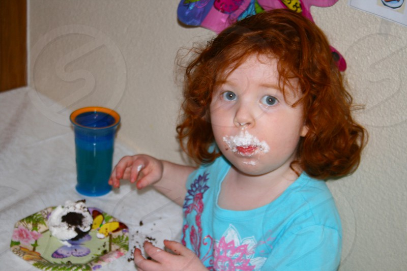 Young girl with cake icing mustache. photo