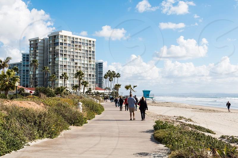 People walk on a sidewalk near the oceanfront in Coronado California located in San Diego County. photo
