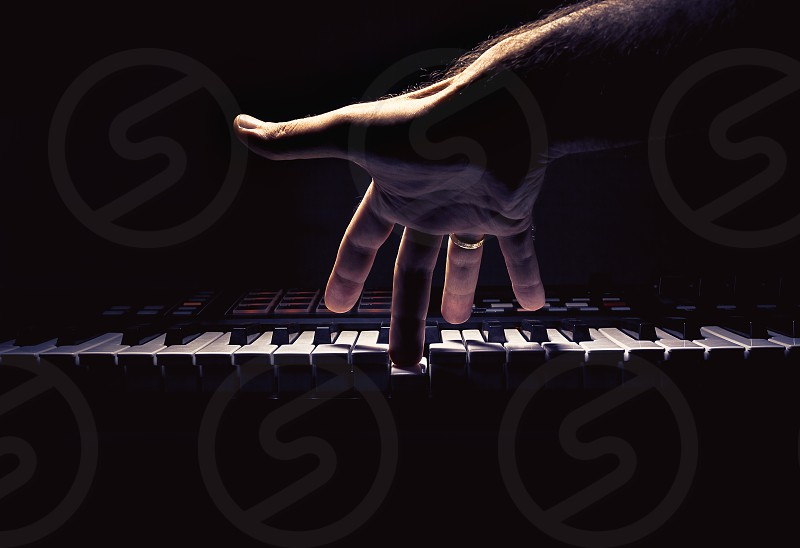 Playing a keyboard one male hand playing accentuated contrasts.   photo