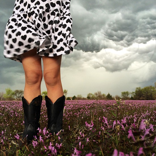 Girl dress boots wind clouds field flowers storm nature sky. photo
