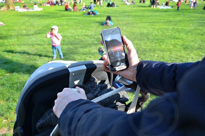 man in blue jacket pushing stroller and checking phone in park photo
