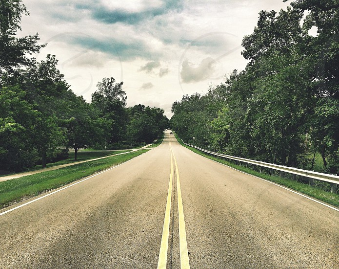 gray concrete road between green treeline during daytime photo