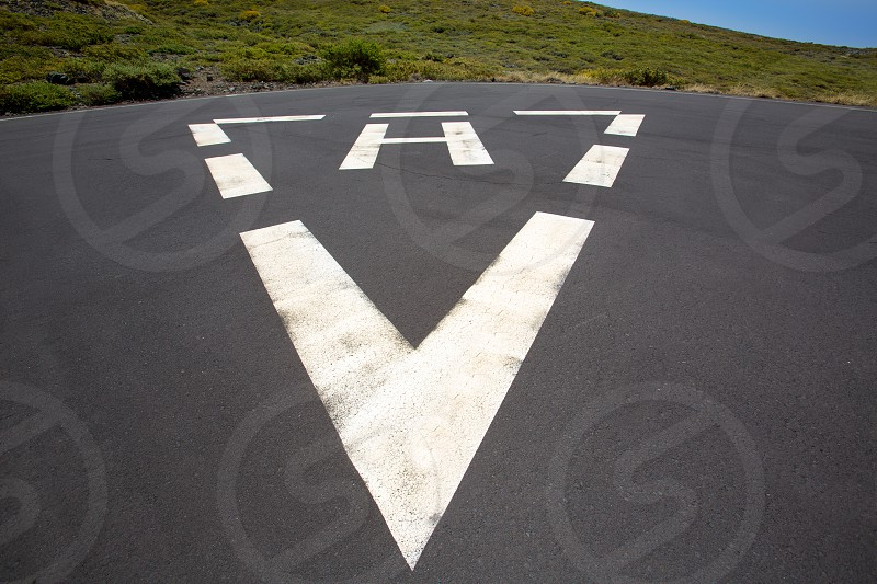 heliport triangle white soil painted sign in pavement photo