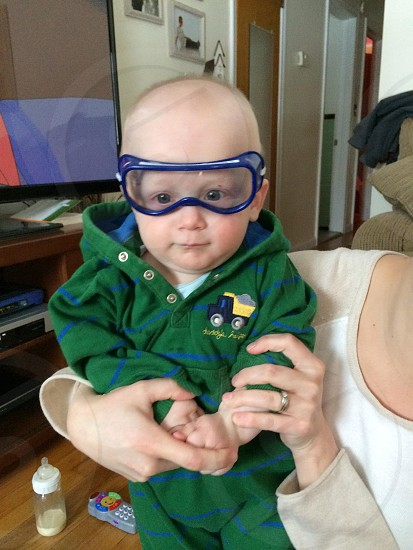 baby in blue goggles and green and blue striped romper photo