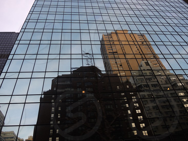 brown and black buildings reflection on glass building photo