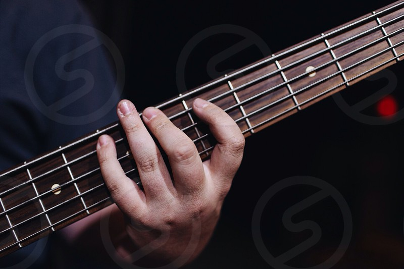 person holding guitar neck photo
