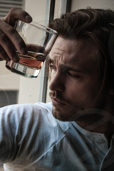 Man leaning against window with whiskey. photo