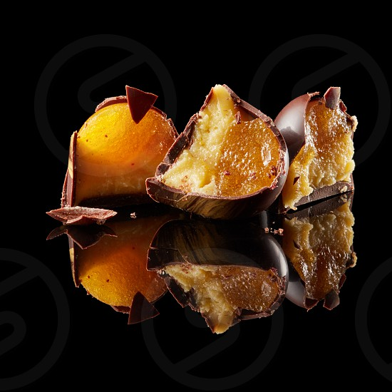delicious chocolates candies in a cut on a black background photo