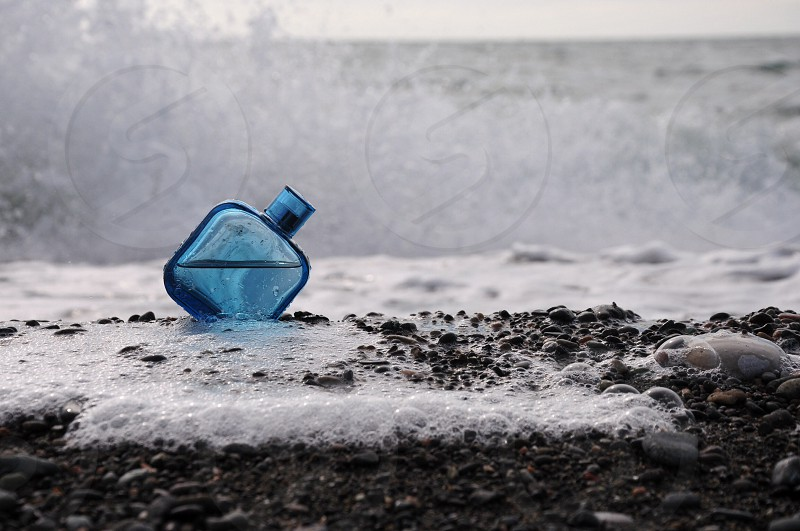 blue tinted glass bottle on soil photo