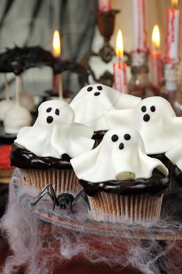Smorgasbord  сupcakes in chocolate glaze decorated  marzipan ghosts on Halloween  photo