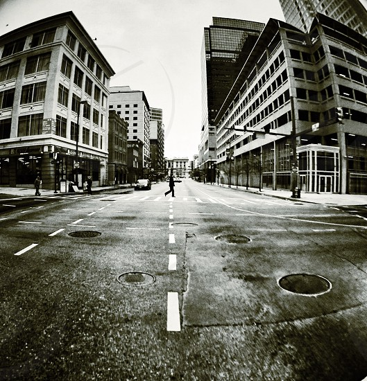 man walking in pedestrian lane grayscale photography photo
