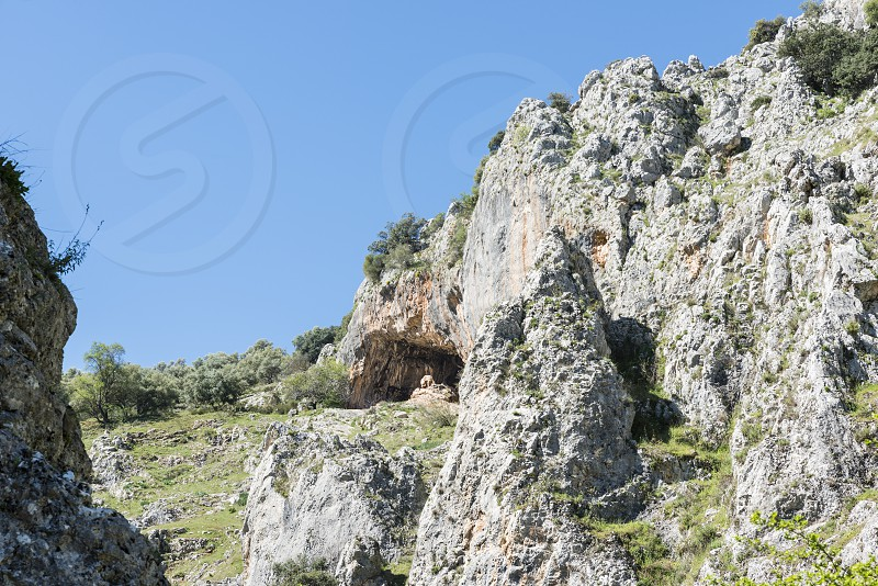 rocks with old ancient caves where people used to live and blue sky in andalusia with green grass landscape photo
