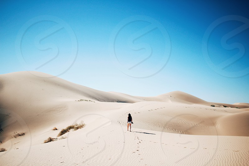 person walking on brown sandy desert under white cloudy blue sky photo