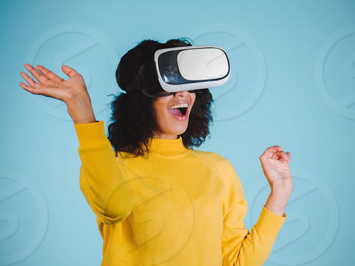 Attractive african woman wearing virtual reality goggles. VR headset. Happy young girl with glasses playing game. Studio shoot photo