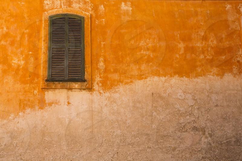Ciutadella Menorca wooden shutter window on grunge yellow downtown wall at Balearic islands photo
