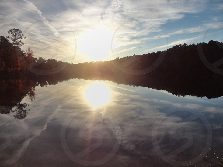 tree lined body of water with sunset photo