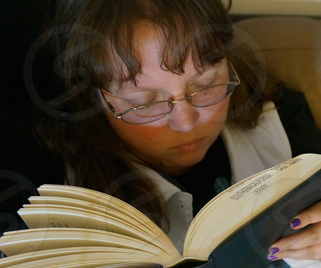woman in eyeglasses reading a book photo