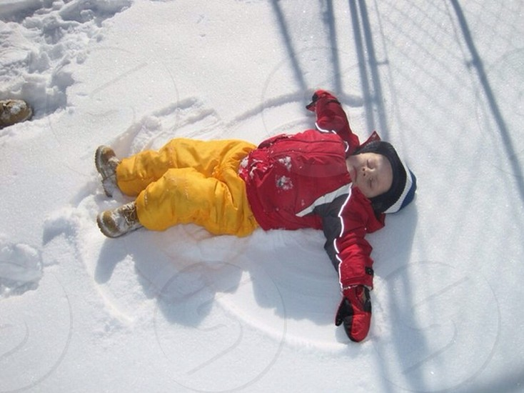 boy lying on snow photo