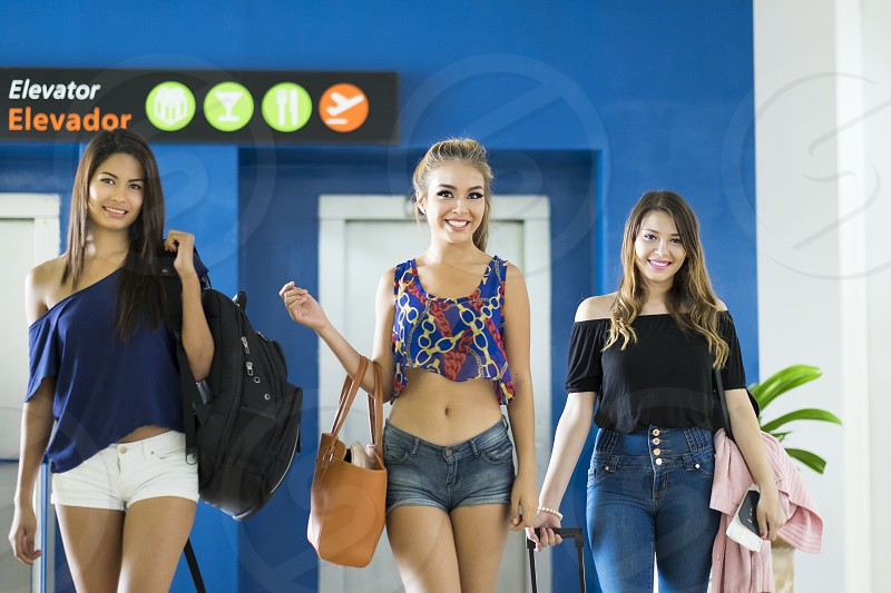 Three female teenagers with luggange are coming out of an elevator at airport terminal photo