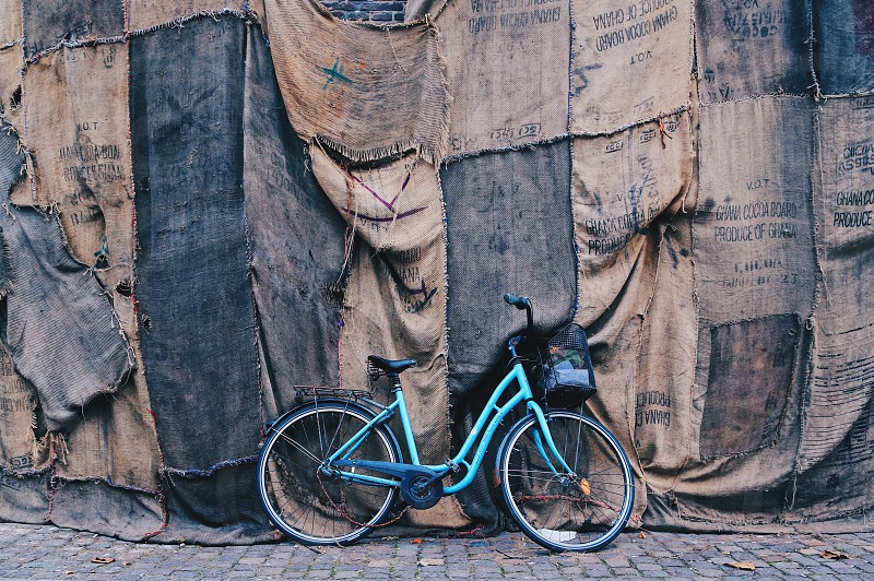 blue step through bicycle  beside a wall covered with brown and black distress textile photo