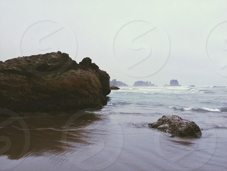 view of seashore with big rock photo